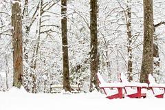 Drei rote Adirondack-Stühle, die in einer schneebedeckten bewaldeten Einstellung, umfasst im Schnee sitzen Stockfotos