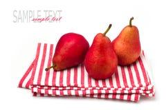 Drei rote Birnen auf gestreifter Tischdecke Stockbilder