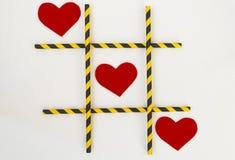 Drei rote geglaubte Herzen werden in einem Tic-TACzehenspiel, in einem Gitter auf einem weißen Hintergrund ausgerichtet Das Gitte lizenzfreie stockfotos