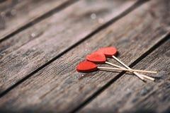 Drei rote Herzen formen auf Stock über hölzernem Hintergrund Rote Rose und Inneres über Weiß Selektiver Fokus Lizenzfreie Stockfotos
