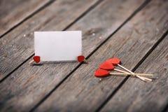 Drei rote Herzen formen auf Stock mit Papierkarte über hölzernem Hintergrund Rote Rose und Inneres über Weiß Selektiver Fokus Cop Stockfotos