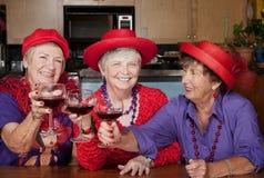 Drei rote Hutdamen, die mit Wein rösten Lizenzfreie Stockbilder