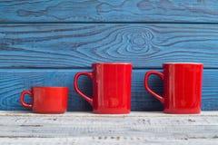 Drei rote Kaffeetassen auf einem Hintergrund von blauen Brettern Stockfotos