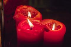 Drei rote Kerzen, die in der Dunkelheit brennen Lizenzfreie Stockfotos