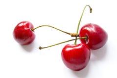 Drei rote Kirschen auf Weiß Stockfoto