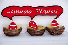 Drei rote Ostereier mit komischen Sprache-Ballon-Franzosen Joyeuses Paques bedeutet fröhliche Ostern Lizenzfreie Stockbilder