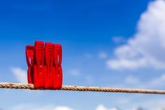 Drei rote Plastikwäscheklammern hängen an einer Wäscheleine und hell Lizenzfreies Stockfoto