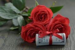 Drei rote Rosen und Bündel Dollar Stockfotografie