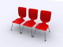 Drei rote Stühle in einer Reihe Stockfotografie