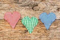 Drei rustikale Herzen auf altem hölzernem Hintergrund für romantische Liebeskarte Stockbilder