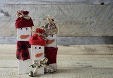 Drei rustikale Schneemänner, die auf Holzoberfläche mit einem hölzernen Hintergrund stehen stockbild