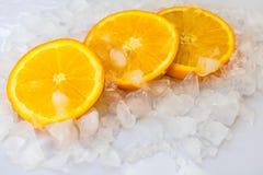 Drei saftige orange Scheiben auf Eis lizenzfreies stockfoto