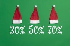 Drei Santa Claus-Hüte auf einem grünen Hintergrund stockfotografie