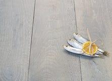 Drei Sardinen mit Zitrone auf Holztisch Lizenzfreies Stockfoto