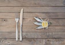 Drei Sardinen und Gabel mit Messer Stockfoto