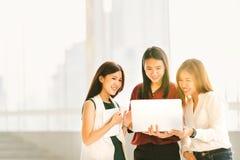 Drei schöne asiatische Mädchen auf zufälligem Geschäftstreffen mit Laptopnotizbuch und digitaler Tablette bei Sonnenuntergang stockfotografie