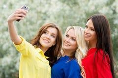 Drei schöne Freundinnen, die durch das Nehmen von selfies modern sind Stockfotos