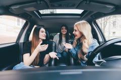 Drei schöne junge Freundinnen haben Spaß zusammen im O-Auto, während sie auf eine Autoreise zusammen ihre Sommerferien anstreben Stockbild