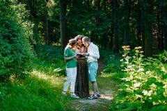 Drei schöne junge multiethnische Freunde besprechen das Buch im Wald das Buch im Wald einer von lesend Lizenzfreies Stockbild