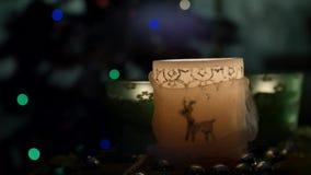 Drei schöne Kerzen auf Hintergrund des blinkenden Weihnachtsbaums stock video