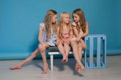 Drei schöne Kleider der kleinen Mädchen arbeiten Porträtschwestern um lizenzfreie stockfotos