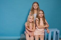 Drei schöne Kleider der kleinen Mädchen arbeiten Porträtschwestern um stockbilder