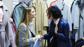 Drei schöne Mädchen, die über Kleid im Shop kämpfen stock footage