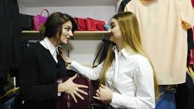 Drei schöne Mädchen, die über Tasche im Shop kämpfen stock video footage