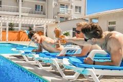 Drei schöne Mädchen, die Cocktails nahe dem Pool trinken Lizenzfreie Stockbilder