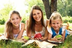 Drei schöne Mädchen, die im Park sich entspannen Lizenzfreie Stockfotografie
