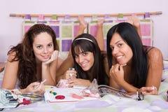 Drei schöne Mädchen, die zusammen auf dem Bett genießen Lizenzfreie Stockfotos