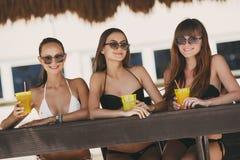 Drei schöne Mädchen in einer Bar auf dem Strand Stockbilder
