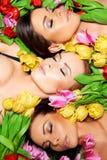Drei schöne sinnliche Frauen mit bunten Tulpen Stockfoto