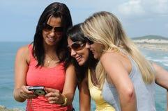 Drei Schönheiten, die selfie auf dem Strand nehmen lizenzfreies stockfoto