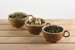 Drei Schalen mit grünen Teeblättern auf einem weißen Hintergrund Stockbilder