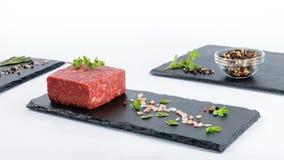 Drei Schieferbretter mit Stück rohem Rinderhackfleisch, Glasschüsselesprit Stockbild