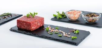 Drei Schieferbretter mit Stück rohem Rinderhackfleisch, Glasschüsseln wi Lizenzfreie Stockfotos
