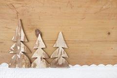 Drei schneebedeckte Weihnachtsbäume auf hölzernem Hintergrund Stockfoto