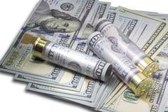 Drei Schrotflintenoberteile luden mit hundert US-Dollar Banknoten auf unterschiedlichem USA-Dollarscheinhintergrund Lizenzfreie Stockbilder