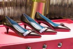 Drei Schuhe dunkle Farbe mit einem flachen Absatz auf einem Stand der rosa Farbe Stockbild