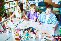 Drei Schulkinder, die Bilder malen Stockbild