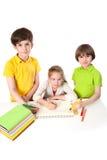 Drei Schulkinder zeichnen in das Notizbuch Lizenzfreies Stockfoto