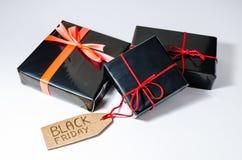 Drei schwarze eingewickelte Geschenkboxen mit einer roten Schnur und Black Friday-Verkäufen etikettieren auf einer Pappe Stockbilder
