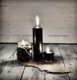 Drei schwarze Kerzen und altes Manuskript mit Pentagram auf Holztisch Lizenzfreie Stockfotos