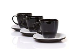 Drei schwarze Schalen auf Stapel der Platten lizenzfreies stockbild