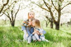 Drei Schwestermädchen, die auf dem grünen Park im Freien spielen Lizenzfreie Stockbilder