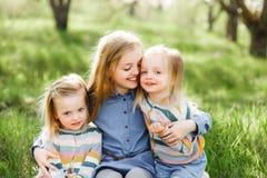 Drei Schwestermädchen, die auf dem grünen Park im Freien spielen Stockfotografie
