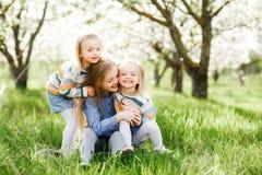 Drei Schwestermädchen, die auf dem grünen Park im Freien spielen Stockbilder