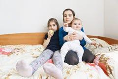 Drei Schwestern, die auf der Couch sitzen stockbild