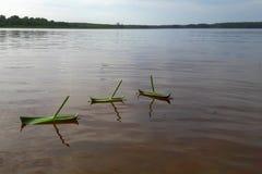 Drei selbst gemachte Boote vom Gras schwimmen in Folge auf die ruhige Oberfläche des Sees in Finnland stockfoto